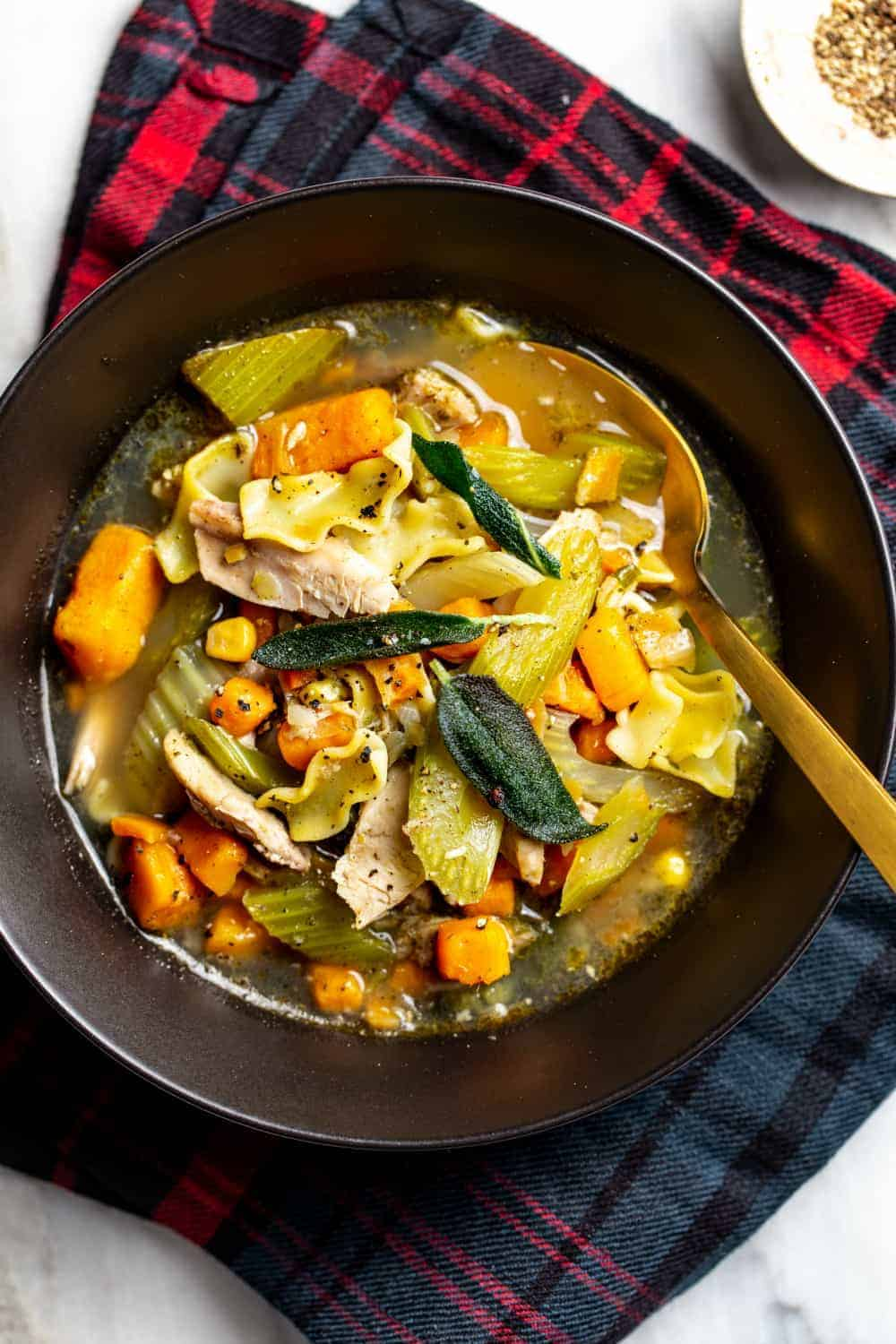 Gold spoon in a bowl of turkey noodle soup garnished with crispy sage