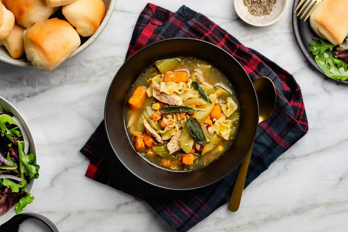Turkey noodle soup in a black bowl on top of a plaid napkin on a marble surface