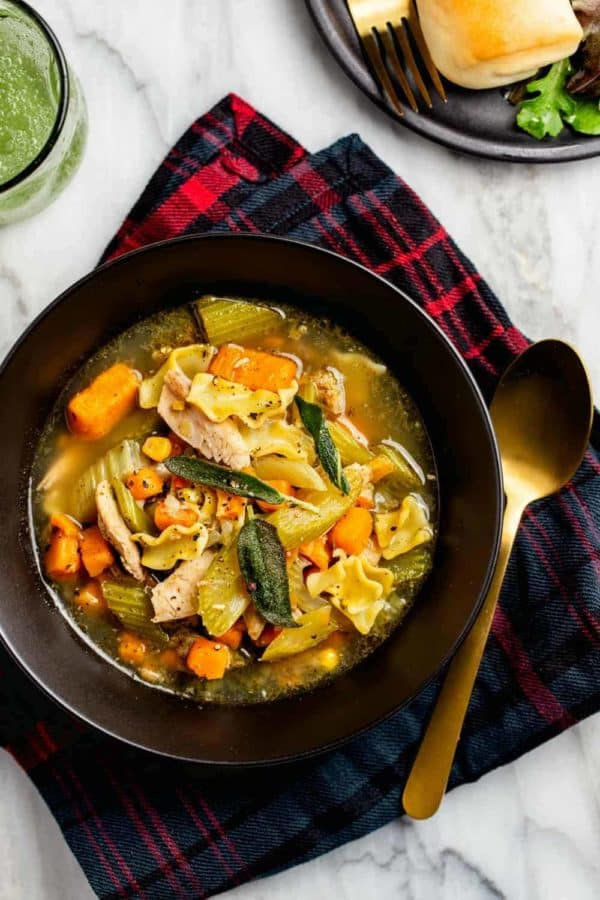 Easy turkey noodle soup made with leftover turkey in a black bowl by a gold spoon