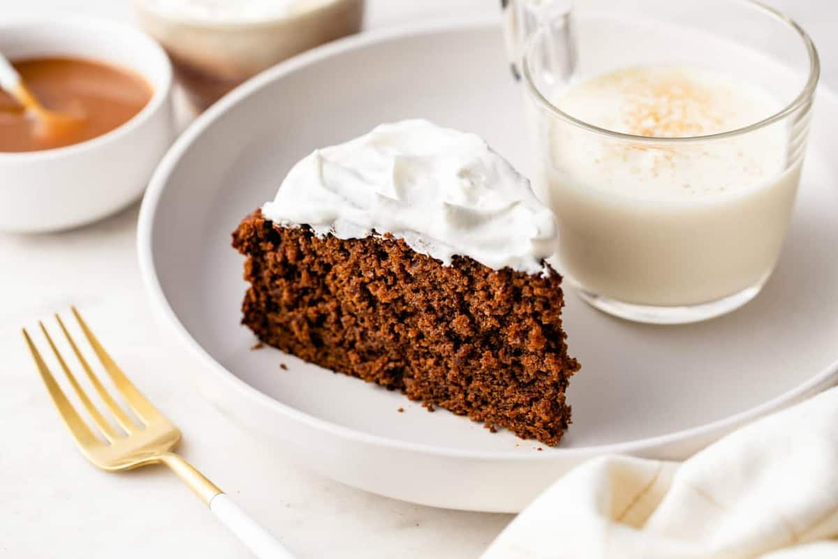 whipped-cream-topped gingerbread cake on a white plate next to a glass of eggnog