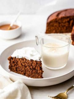 Slice of gingerbread cake and a glass of eggnog on a white plate