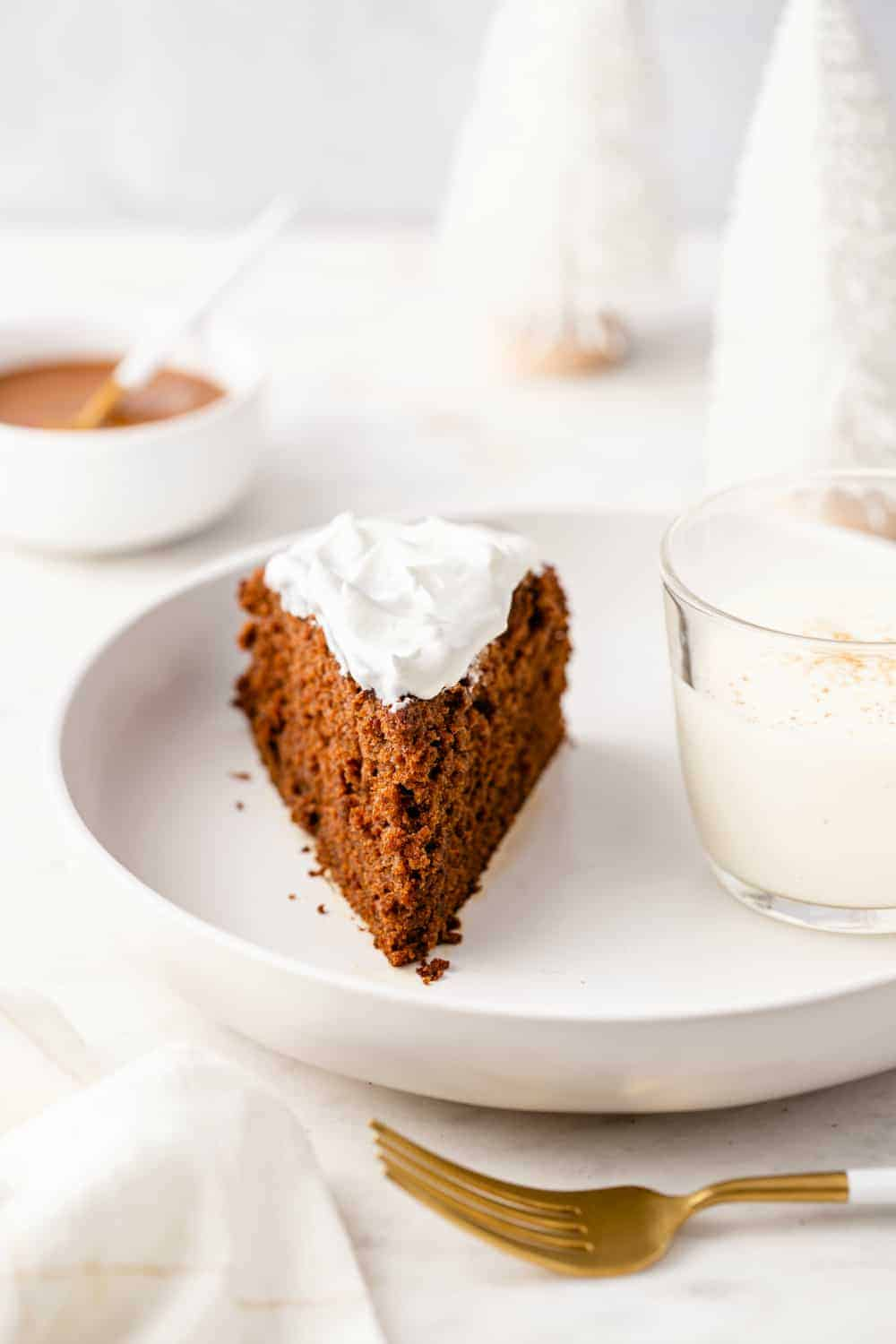 Glass of eggnog and a slice of gingerbread caked topped with whipped cream on a white plate