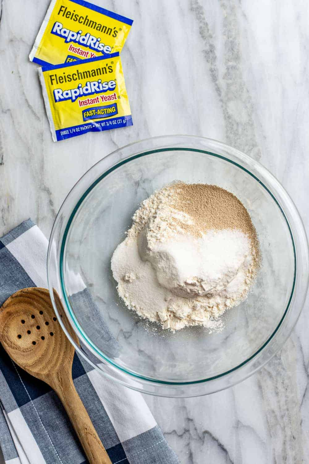 Dry ingredients for 30 minute pizza crust in a glass mixing bowl on a marble surface