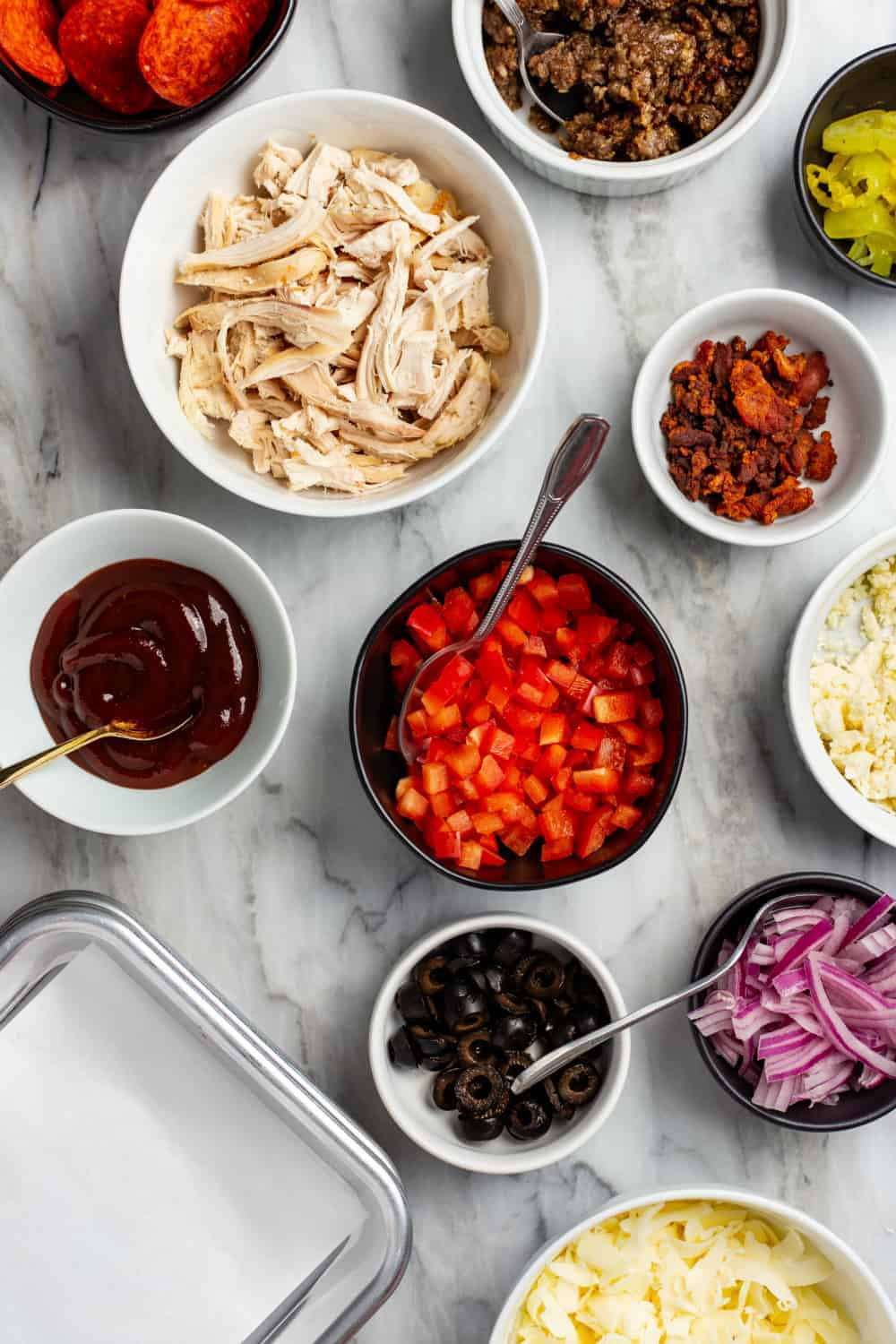 Assorted toppings and sauces for a DIY pizza bar in small bowls