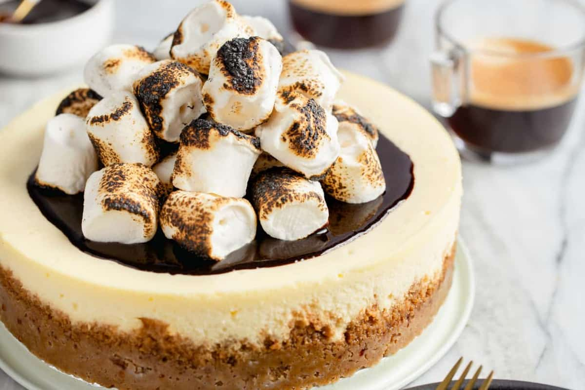 Toasted marshmallows piled on top of a cheesecake on a serving platter