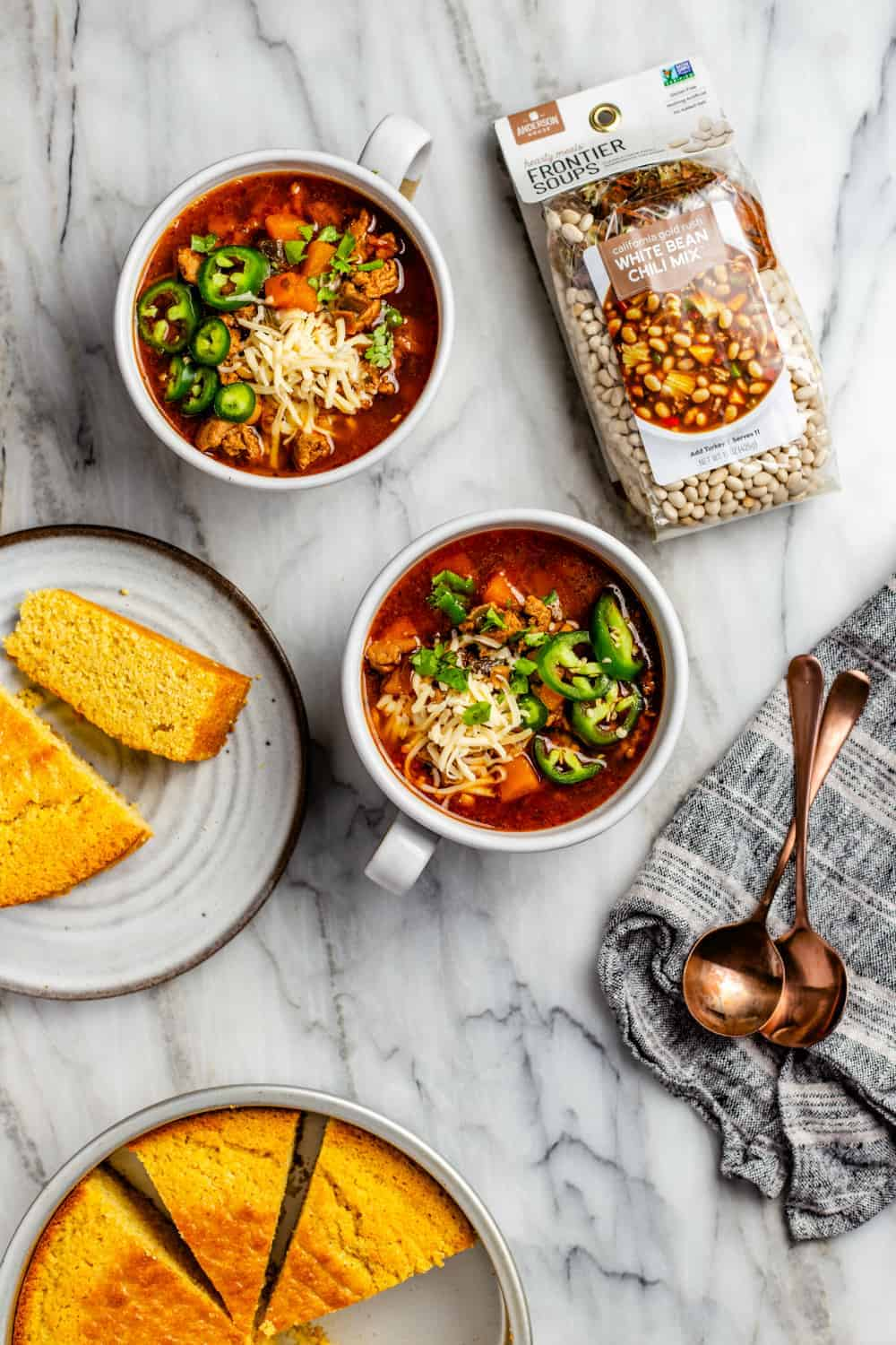 Bowls of white bean chicken chili next to plates of cornbread