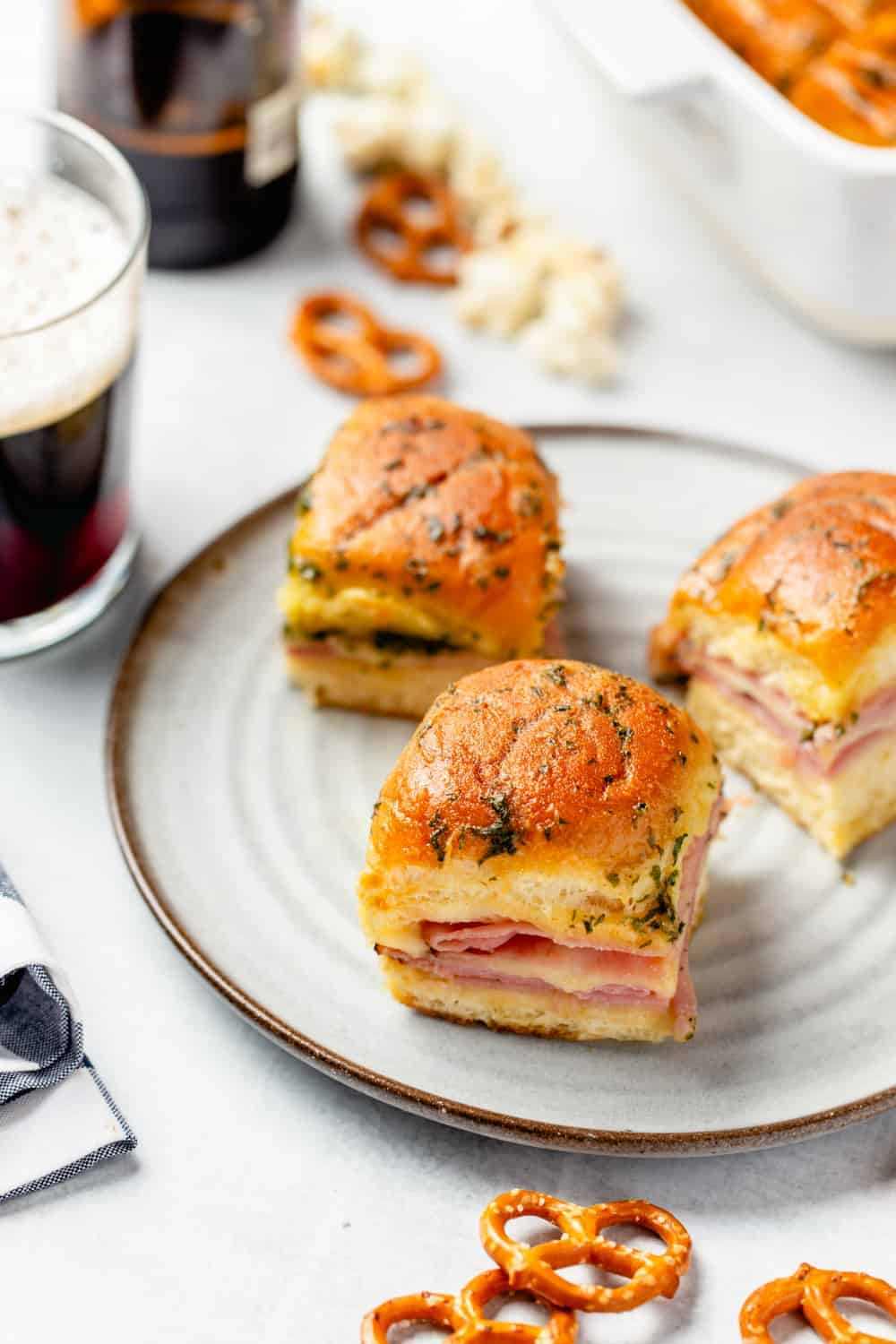 Plate of three ham and cheese sliders next to a glass of beer