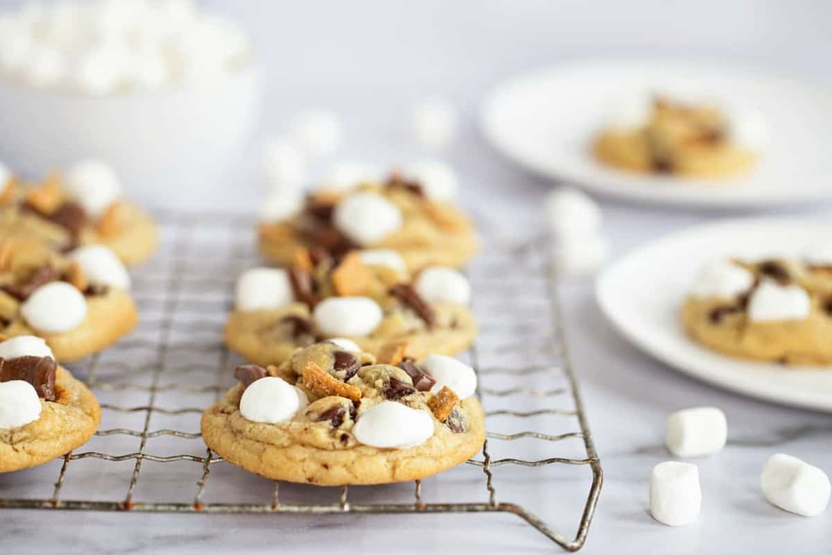 S'mores cookies lined up on a metal cooling rack with mini marshmallows scattered on the countertop