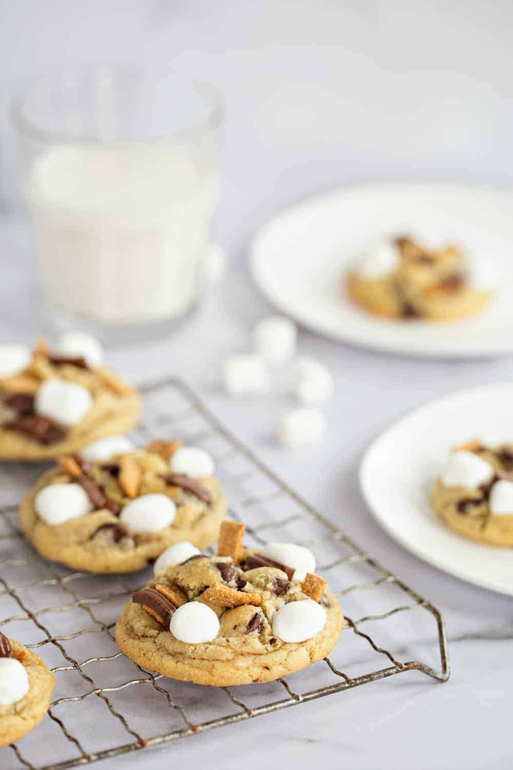 S'more's cookies on a metal cooling rack with white plates with cookies on them in the background