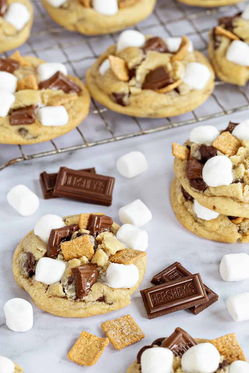 S'mores cookies scattered on a marble surface with mini marshmallows and chocolate pieces
