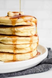 Syrup being drizzled over a stack of fluffy Bisquick pancakes on a white plate
