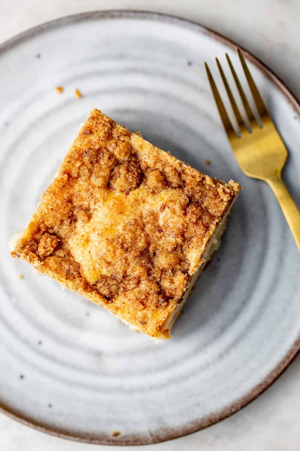 Overhead view of cinnamon coffee cake topped with cinnamon streusel on a white plate next to a gold fork