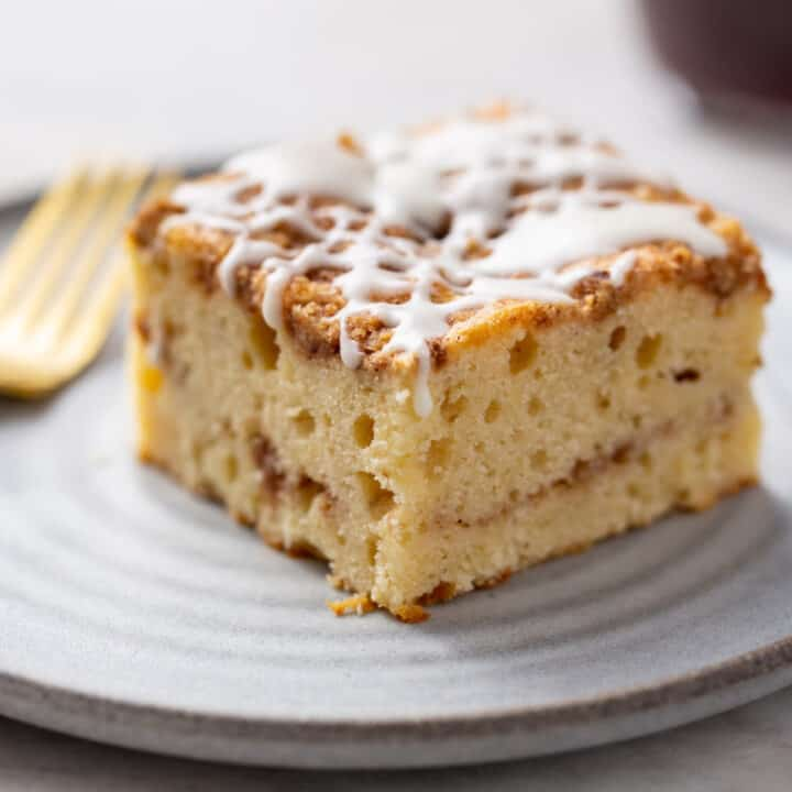 Close up side view of a slice of cinnamon coffee cake on a white plate. Cake topped with vanilla glaze and showing cinnamon streusel in the center