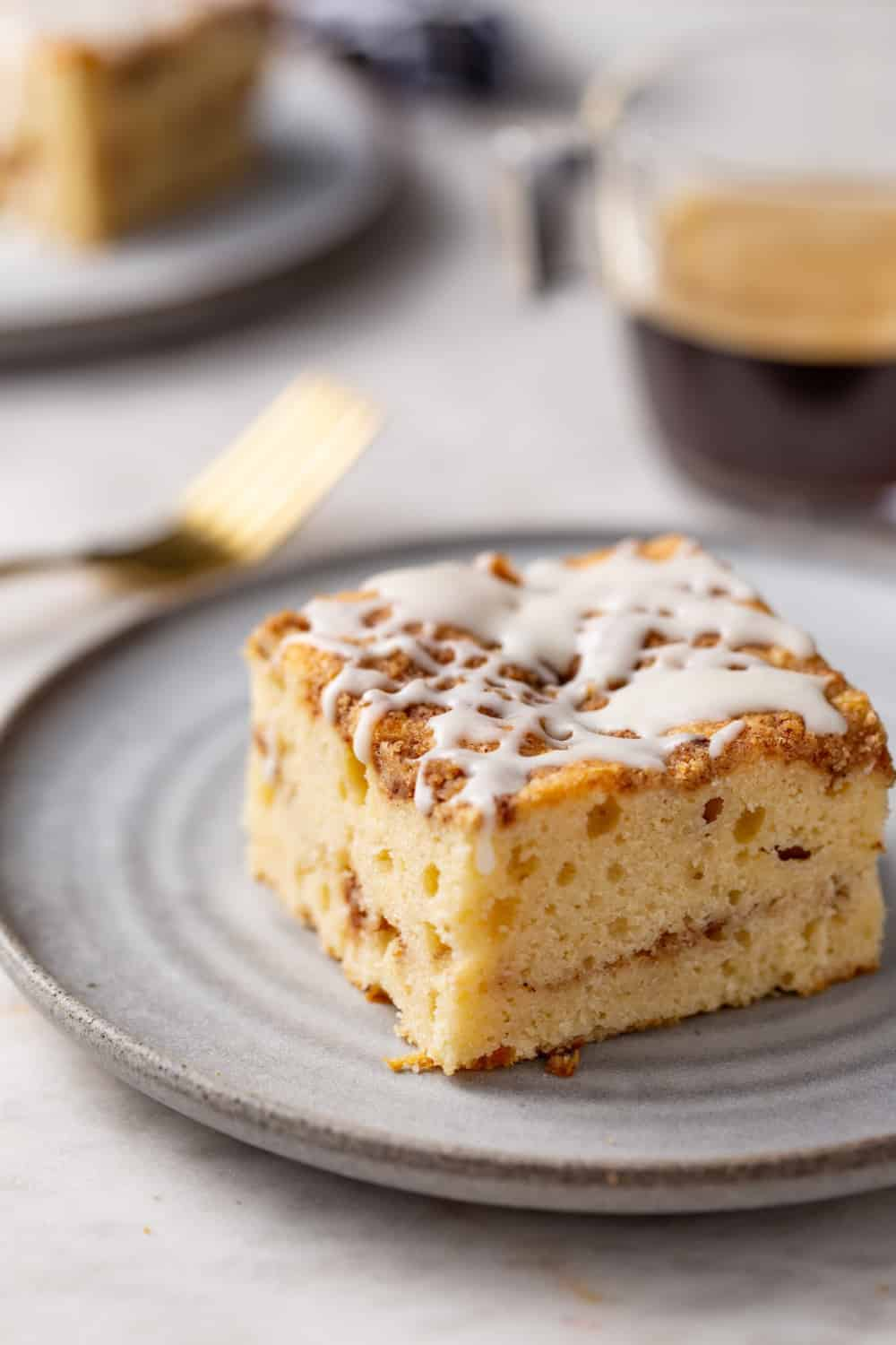 Angled view of cinnamon coffee cake on a white plate with gold fork and cup of espresso visible in the background. Cake topped with vanilla glaze