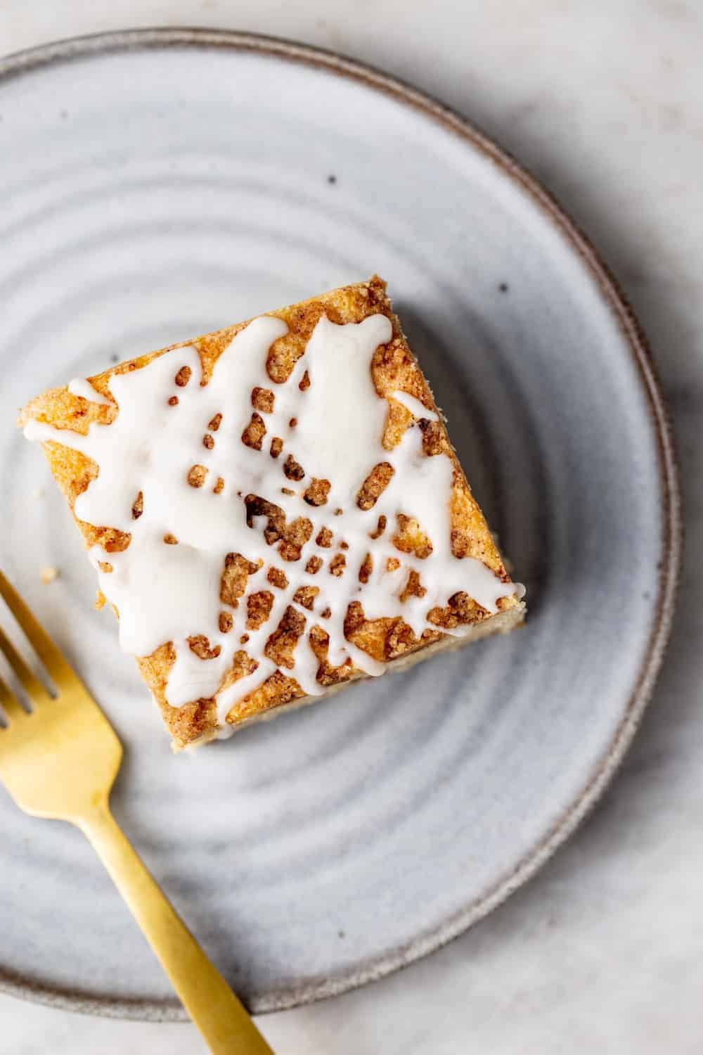 Overhead view of a slice of cinnamon coffee cake with vanilla glaze on a white plate next to a gold fork