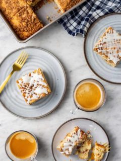 Cake pan with cinnamon coffee cake on a marble counter next to three plates of cinnamon coffee cake and two cups of espresso