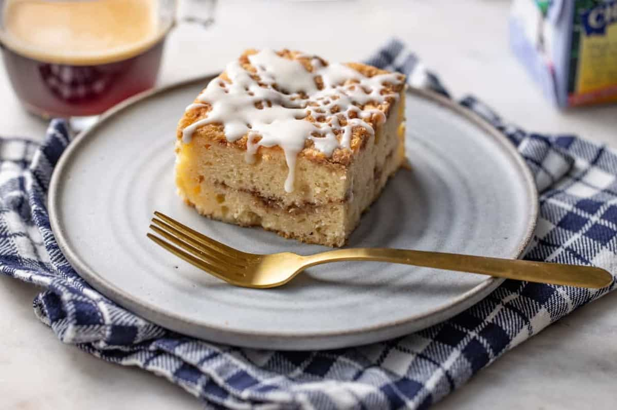 Angled view of a slice of cinnamon coffee cake on a white plate next to a gold fork, showing a line of cinnamon streusel in the middle of the cake