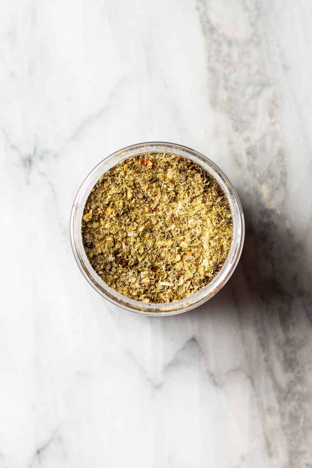 Pizza seasoning for using in homemade meat sauce in a jar on a marble counter