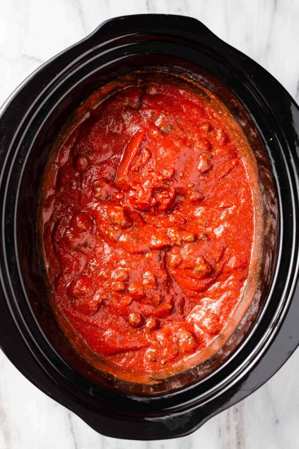 Overhead view of homemade meat sauce in the black crock of a slow cooker