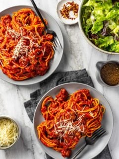 Spaghetti and homemade meat sauce portioned onto two gray plates on a marble surface, topped with parmesan cheese next to a green salad