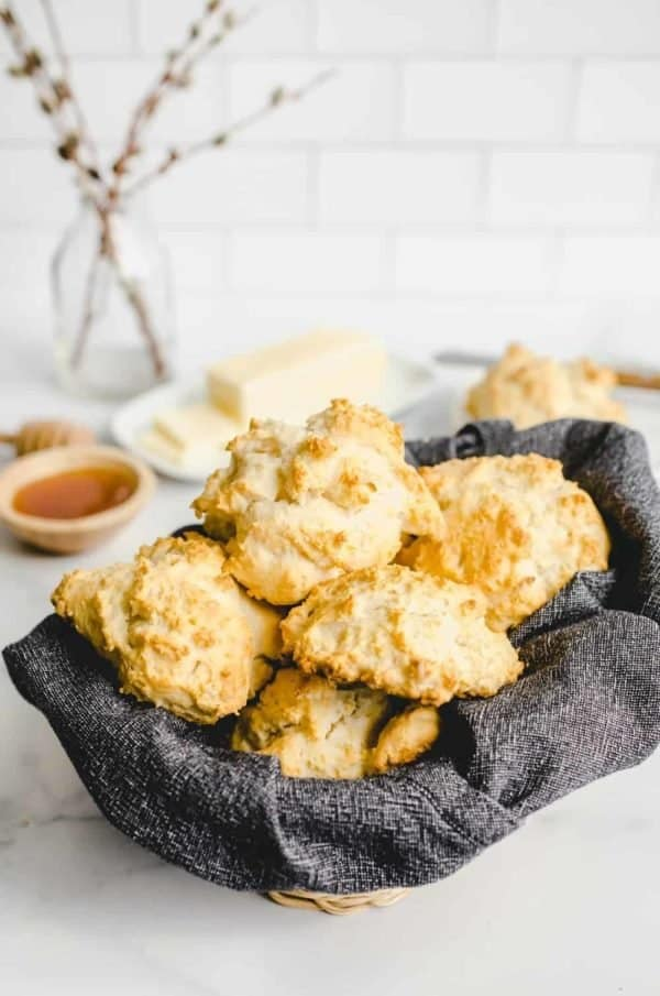 Basket lined with a dark gray napkin and filled with bisquick biscuits on a countertop with butter and honey