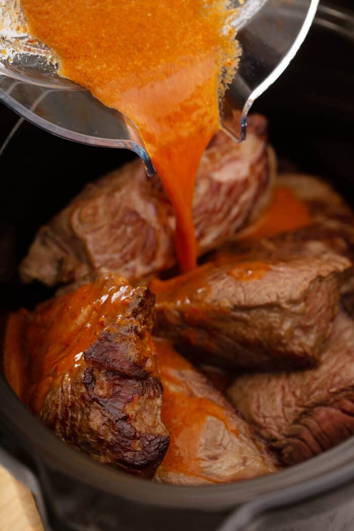 Bowl pouring chipotle sauce over seared beef in a slow cooker