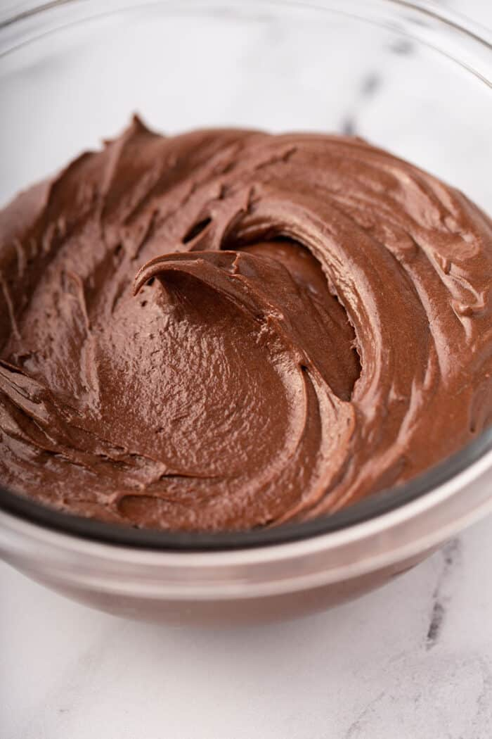 Close up of homemade chocolate frosting in a glass bowl on a marble counter
