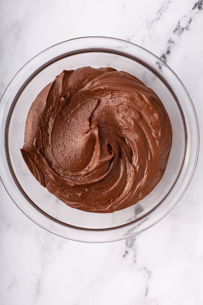 Overhead view of homemade chocolate frosting in a glass mixing bowl on a marble counter