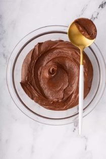 Overhead view of homemade chocolate frosting in a glass bowl with a gold spoon balanced on the edge, holding a dollop of frosting