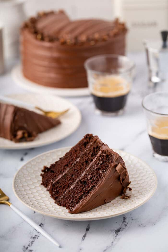 Slice of Hershey's Chocolate Cake with chocolate frosting on a white plate, with more cake and cups of espresso in the background