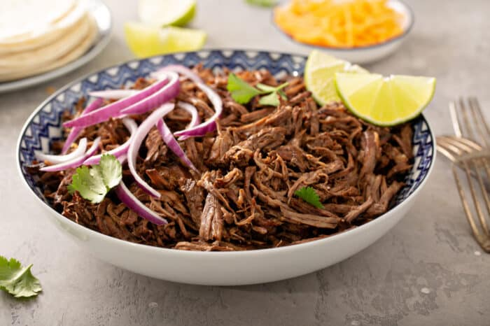 Chipotle barbacoa in a blue and white bowl topped with red onions, cilantro and lime wedges