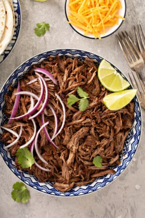 Overhead view of chipotle barbacoa in a blue and white bowl, toped with red onions, cilantro and lime wedges