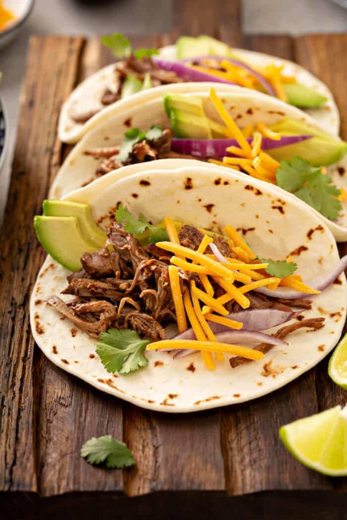 Three Chipotle barbacoa tacos on a wooden platter, topped with cheese and sliced avocado