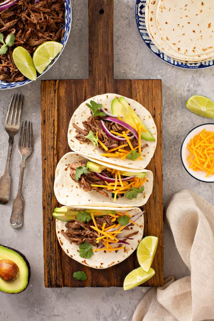 Overhead view of three chipotle barbacoa tacos in flour tortillas lined up on a wooden cutting board