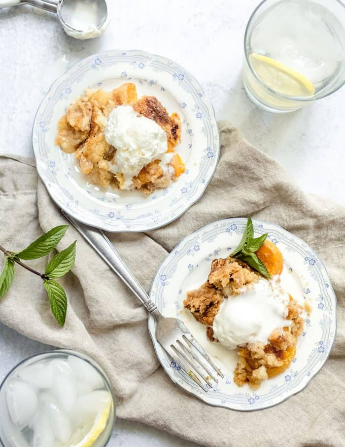 Two white plates each with a serving of easy peach cobbler topped with a scoop of vanilla ice cream