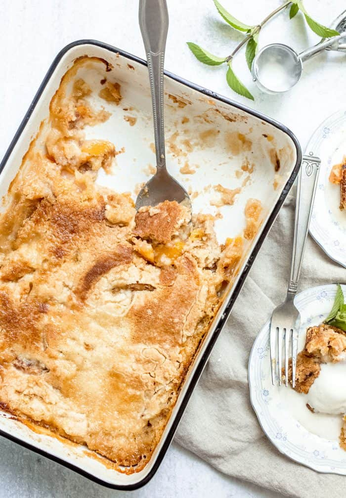 Baking pan of easy peach cobbler with a spoon in it, with several servings removed