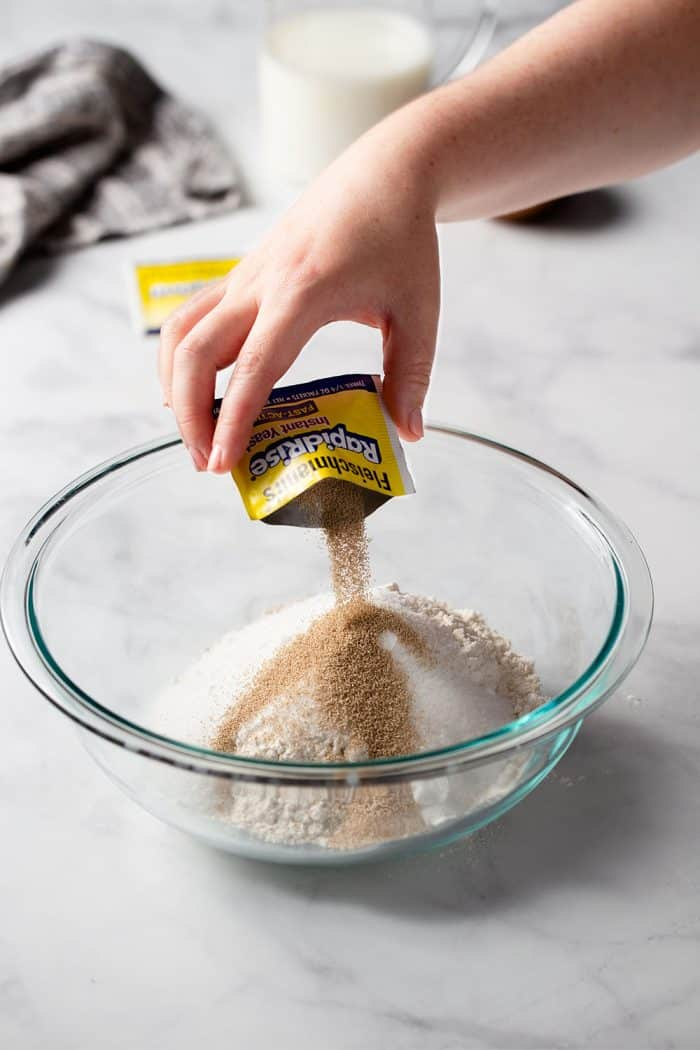 Hand pouring a packet of yeast into a glass mixing bowl with flour for parker house rolls