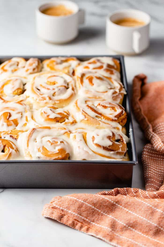 Baking pan of frosted pumpkin spice cinnamon rolls on a marble counter next to a dish towel