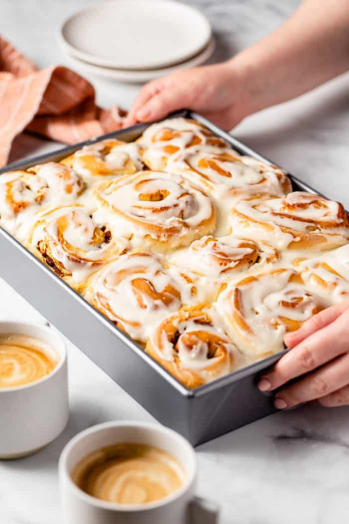 Hands placing a pan of frosted pumpkin spice cinnamon rolls on a marble countertop
