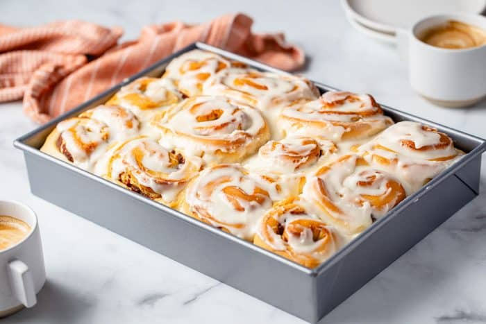 Pan of baked and frosted pumpkin spice cinnamon rolls on a countertop next to a dish towel