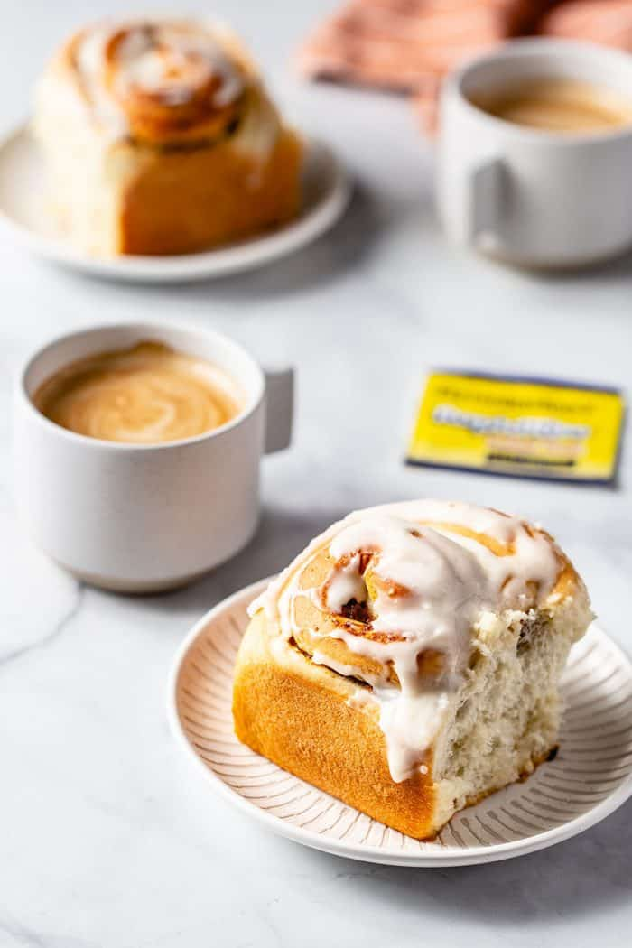 Frosted pumpkin spice cinnamon roll on a white plate with a cup of coffee in the background