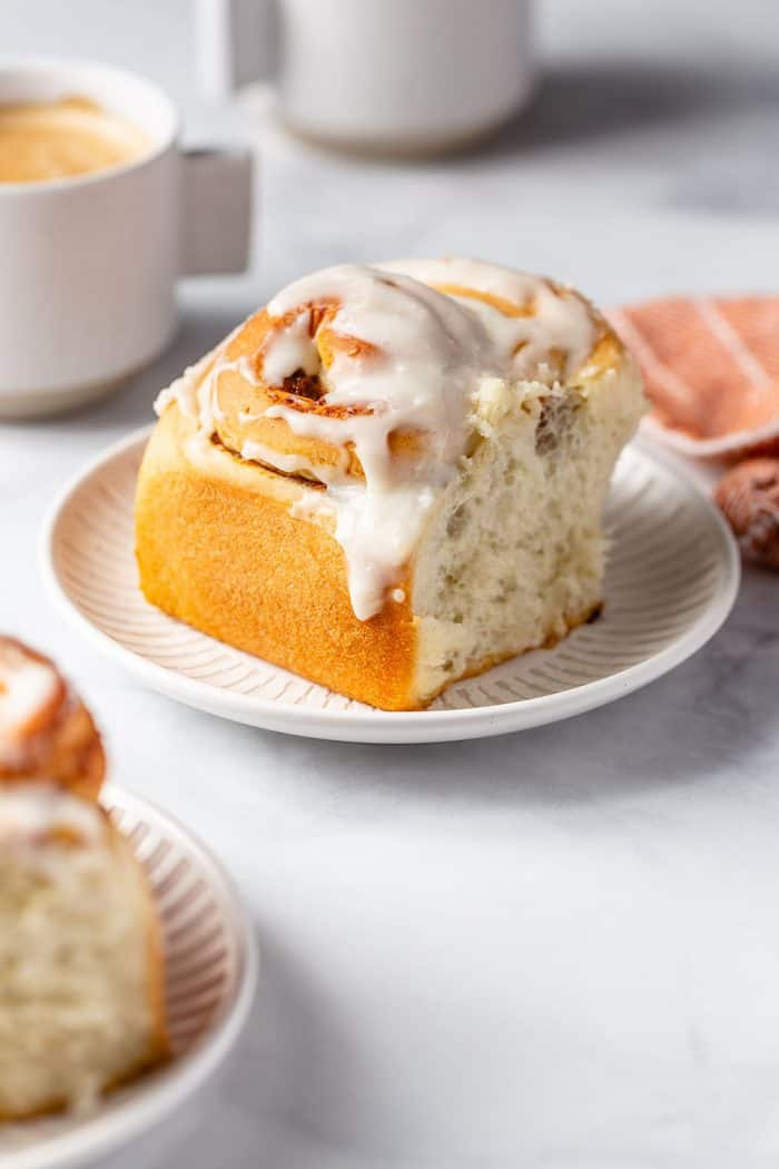 Frosted pumpkin spice cinnamon roll on a white plate with a coffee cup in the background