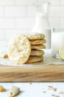 Chewy lime sugar cookies stacked on a parchment-covered cutting board next to a glass of milk