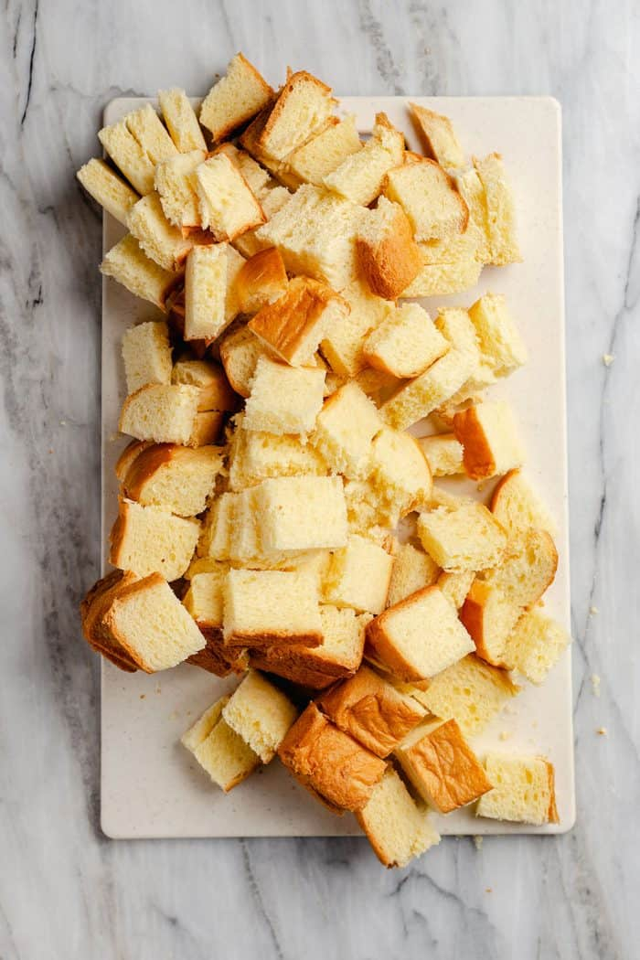 Brioche bread cubes on a white mat set on a marble countertop