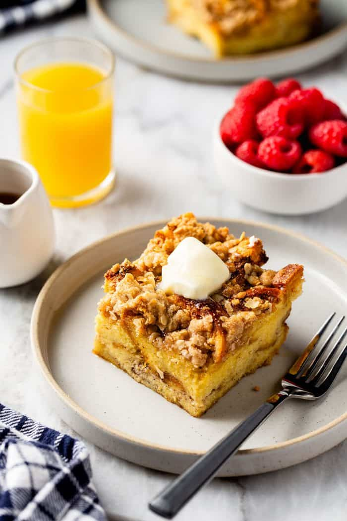 Slice of overnight french toast casserole topped with butter next to a fork on a white plate. Orange juice and fresh raspberries are in the background