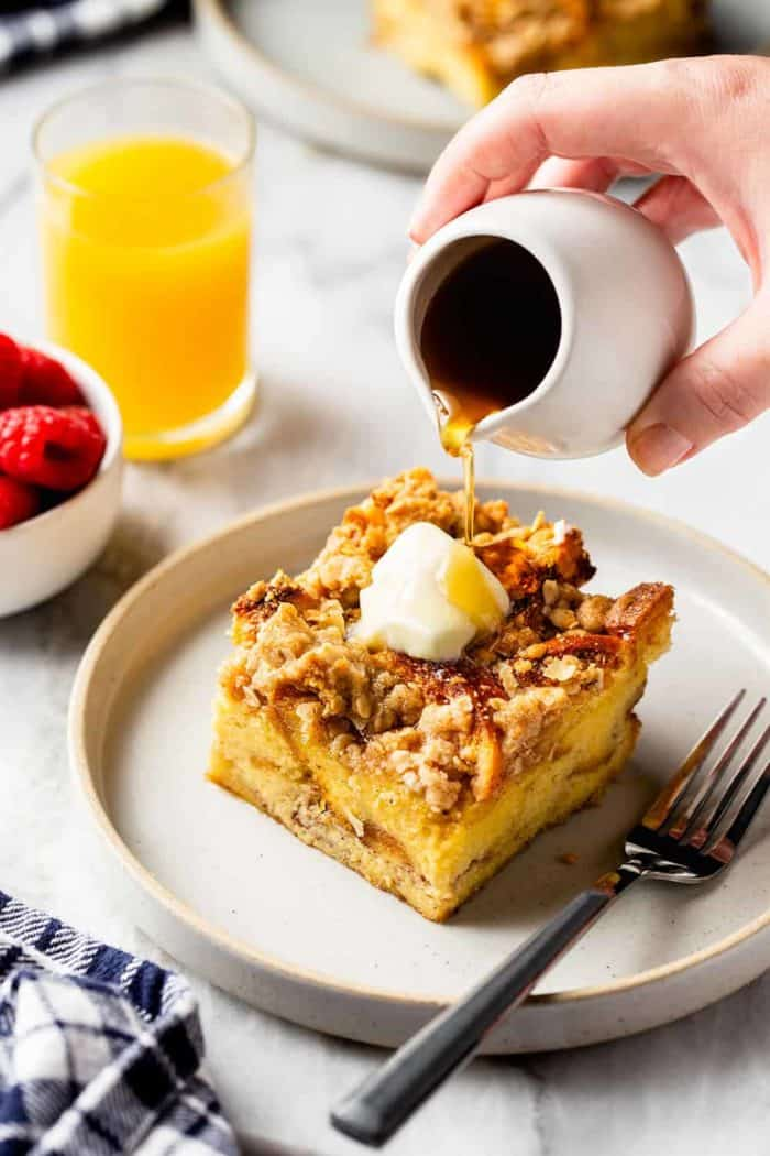 Hand drizzling maple syrup over a slice of buttered overnight french toast casserole on a white plate. A glass of orange juice is in the background
