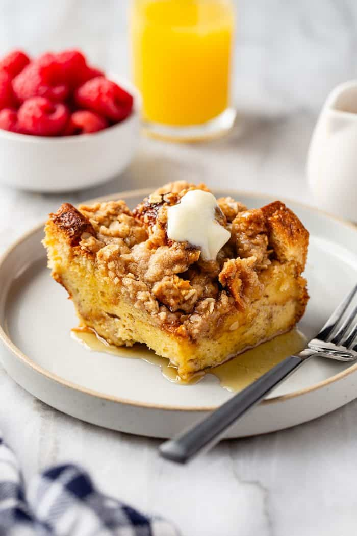 Slice of french toast casserole topped with butter and syrup next to a fork on a white plate. a bowl of raspberries and a glass of orange juice are in the background.