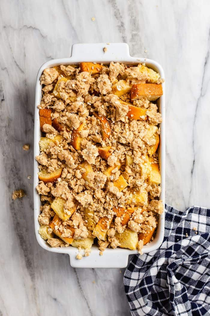 Overnight french toast casserole in a white baking dish, assembled and ready to be baked
