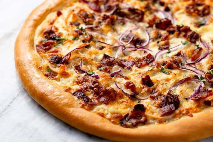 Unsliced chicken bacon ranch pizza set on a marble surface