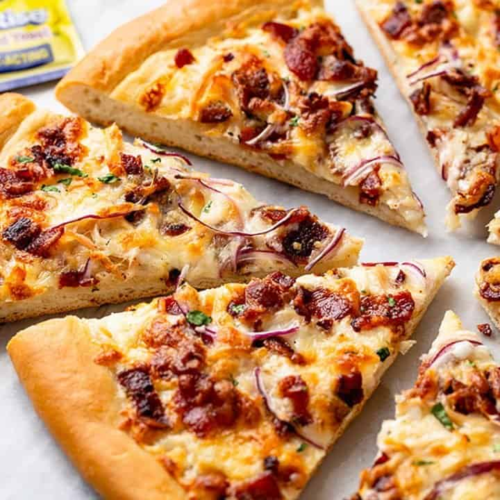 Slices of chicken bacon ranch pizza arranged on a marble surface with a package of yeast in the background